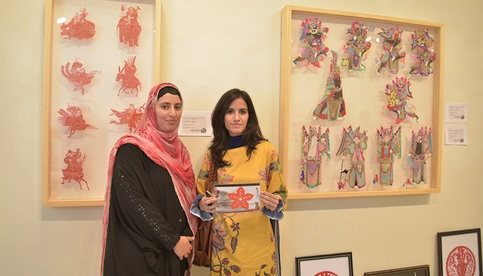 Visitors with Chinese paper cutting art at China Cultural Heritage Week exhibition in Islamabad on 7 July 2017. Photo: Zhu Dan