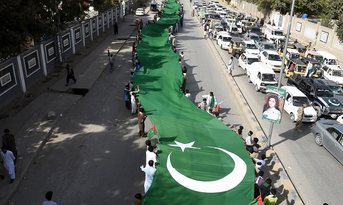 Pakistani residents carry a huge flag during a rally to mark the country's Independence Day in Quetta on August 14, 2017. - AFP/Banaras Khan