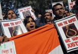 People shout slogans and hold placards during a protest in New Delhi December 29, 2012. An Indian woman whose gang rape in New Delhi triggered violent protests died of her injuries on Saturday in a Singapore hospital, bringing a security lockdown in Delhi and recognition from India's prime minister that social change is needed. REUTERS/Adnan Abidi (INDIA - Tags: CIVIL UNREST CRIME LAW)