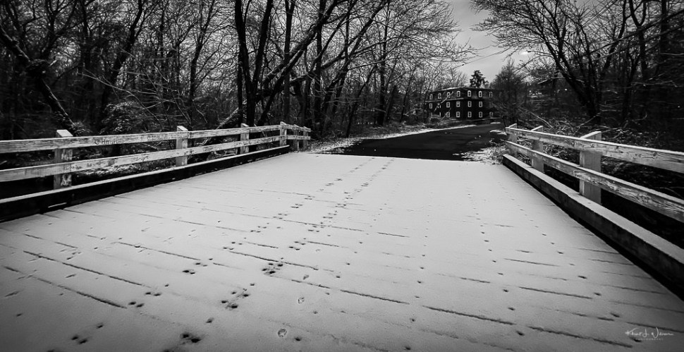 Wooden bridge in the snow with Kingston Mill in the background