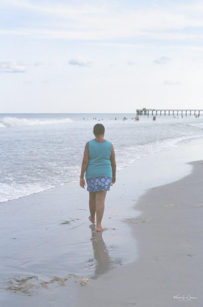 Woman walking on sand at Avalon Beach