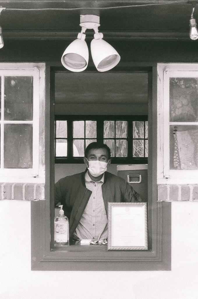 man facing camera through a window