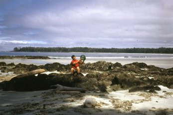 "Ruth Master hold glass ball. Nells Bight, on rocks near the ""old"" ranger cabin."