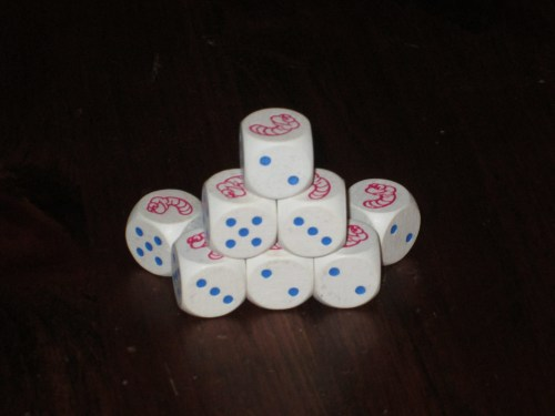 The dice in Pickomino. The dice show numbered sides 1-5, and a worm occupies the sixth side.