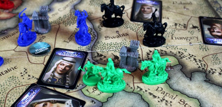 Knights of various player colors, a castle, and some character cards populate the map of Europe game board