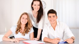 beautiful woman young private teacher helping two students doing their homework