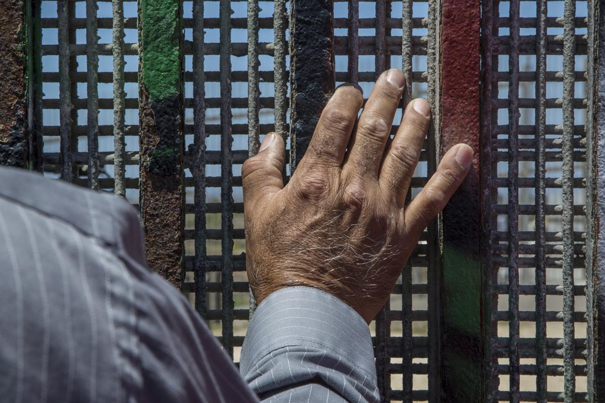 El pastor Guillermo Navarrete de la Iglesia Metodista de México en el muro fronterizo durante un encuentro de la Iglesia Fronteriza en el Parque de la Amistad. El servicio binacional se lleva a cabo en inglés y en español simultáneamente en ambos lados de la frontera. Fotografía: Griselda San Martín