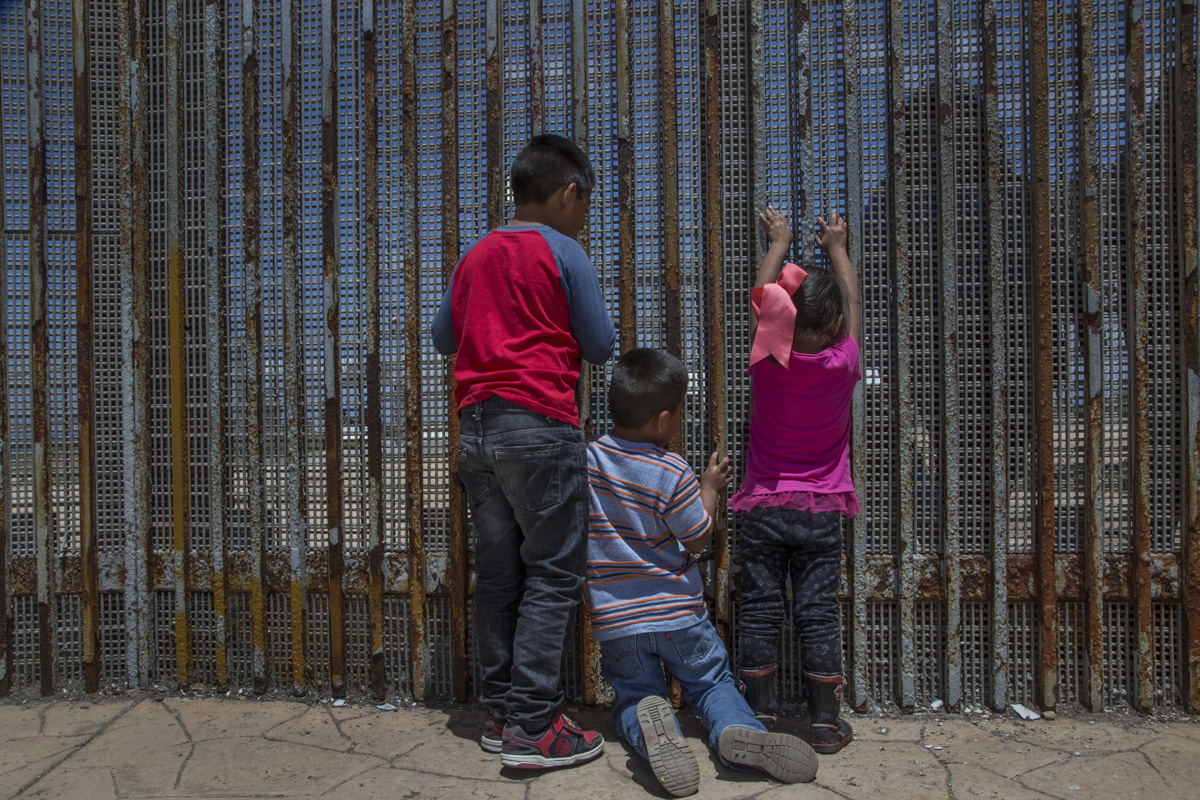 Los hermanos Christian, de 8 años; Angel, de 6, y Sofia, de 4, hablan con sus primos a través de la malla metálica del muro fronterizo del Parque de la Amistad. En este día, conocieron a sus primos y a su tía por primera vez. Fotografía: Griselda San Martín