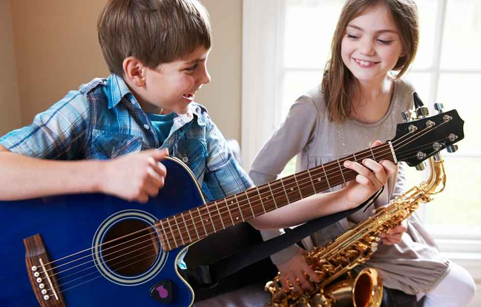 Children playing guitar and saxophone and having fun in their music classes at International School of Music