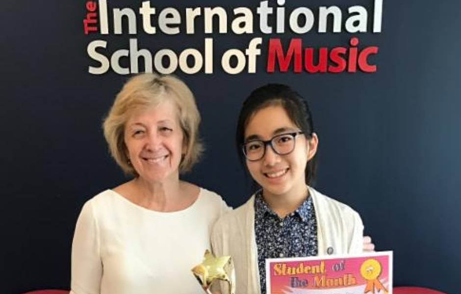 International School of Music student holding student of the month trophy and certificate