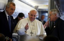 Pope Francis gives a thumbs up next to father Lombardi during his flight to Turkey