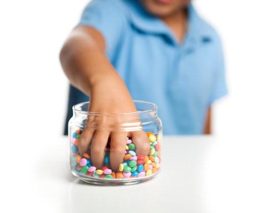 Little boy taking candy from jar