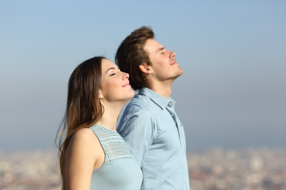 Relaxed couple breathing fresh air with urban background