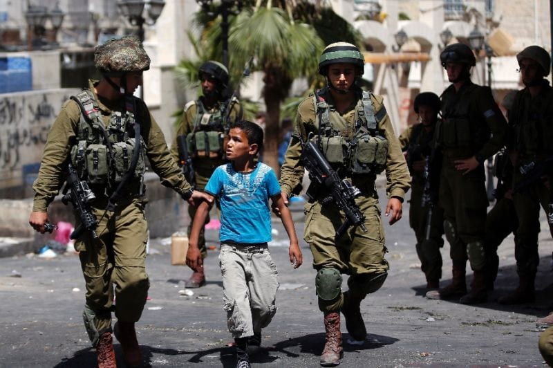 "Israeli soldiers arrest Palestinian boy in West Bank town of Hebron, June 20, 2014. ""Human Rights Watch on Monday accused Israel of 'abusive arrests' of Palestinian children as young as 11 and of using threats to force them to sign confessions."" – AFP"