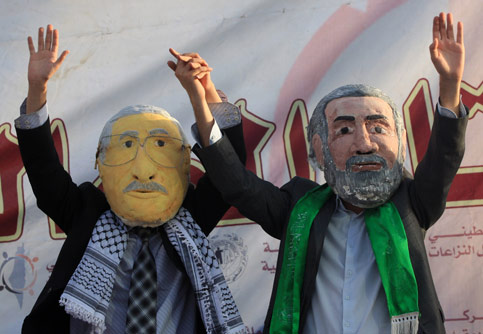 Palestinians in Gaza wearing masks of Fatah leader Mahmoud Abbas and Hamas Prime Minister Ismail Haniyeh call for unity between the feuding groups. (Wissam Nassar/MaanImages)