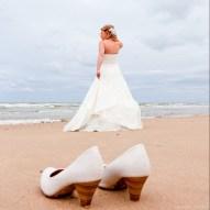 Bruid op het strand van Bergen, schoenen uit