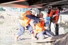 twee monteurs trekken aan ketting tijdens montage van stalen brugdelen