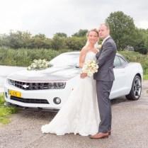 Bruidspaar voor auto bij het water