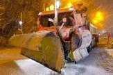 Voorzijde van strooiploeg aan vrachtwagen in de sneeuw