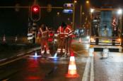 Wegwerkers warmen en drogen asfalt op rijstrook weg