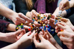 Das Bild zeigt Menschen, die mit Lego-Figuren ein virtuelles Team nachstellen. Bild: Unsplash/Vlad Hilitanu