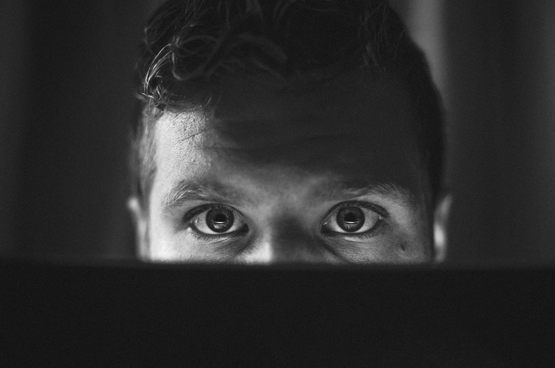 BW photo of man looking over over laptop