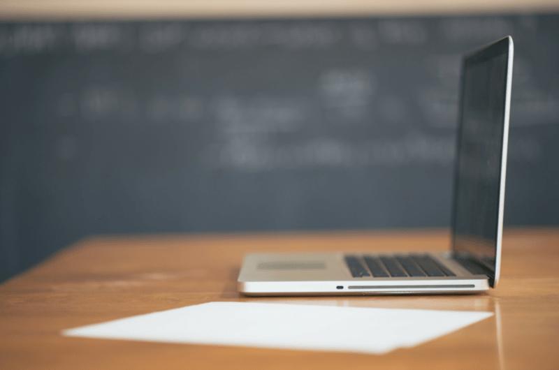 Mac Laptop on Desk with Blackboard in Background