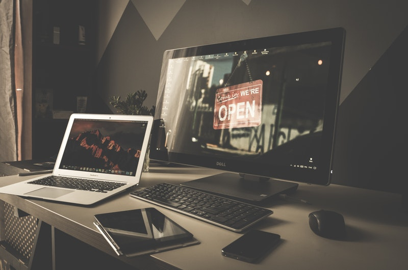 Dell Desktop, Mac Laptop, Tablet and Cellphone on a Desk