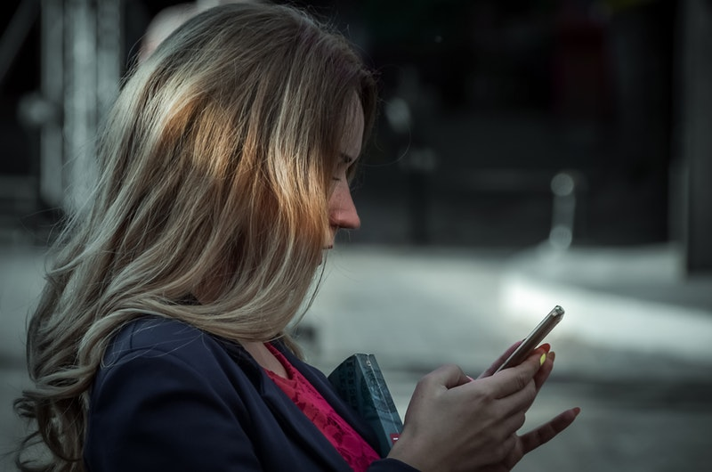 Woman on Mobile Phone Carrying a Book