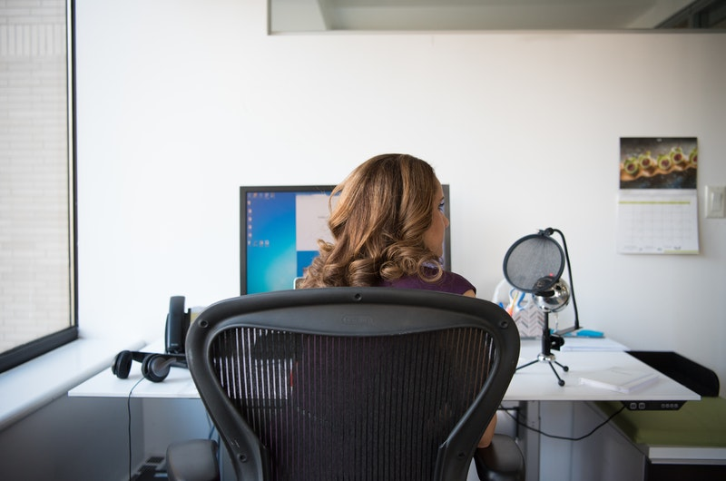 Woman sitting on chair in front of turned on desktop monitor running Windows OS