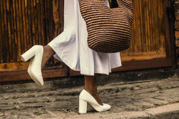 woman wearing white dress and white high heeled shoes while walking on sidewalk