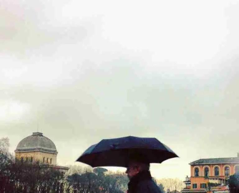A man walks across the Ponte Garibaldi in Rome