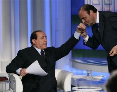 "Conservative leader Silvio Berlusconi, left, puts out his hand for RAI national television network talk show ""Porta a Porta (door to door) host Bruno Vespa to smell it, during the recording of the show, in Rome, Thursday, April 10, 2008. Berlusconi asked Vespa to smell his hand saying it has ""the scent of sainthood"" because of what he believes he's had to go through during the election campaign. Italians go to vote Sunday and Monday for a national parliament and a new premier. (AP Photo/Plinio Lepri)"