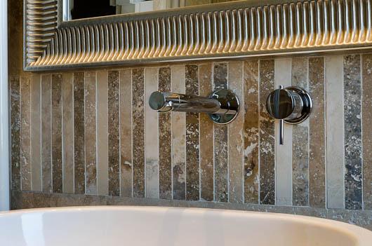 Rivestimento bagno in travertino con specchio con cornice barocca in argento