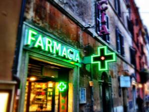 The green neon cross of a farmacia.