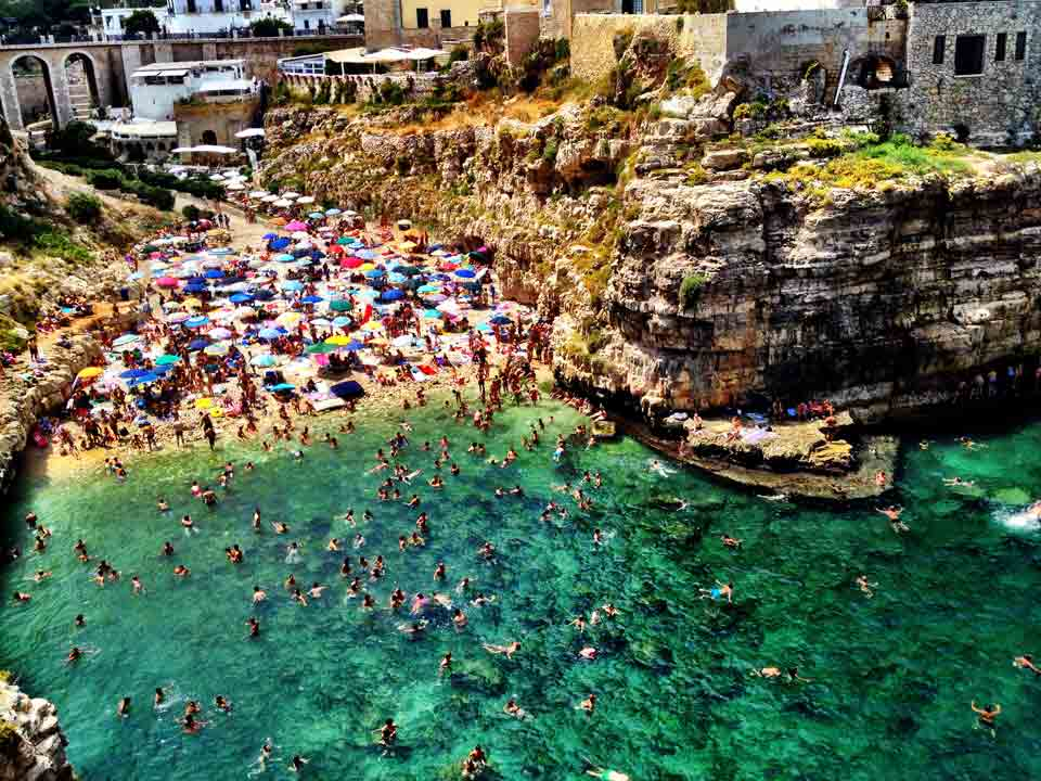 August Italian vacationers flock to seaside havens like Polignano a Mare.
