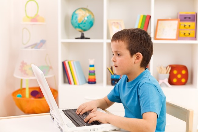 Boy playing or working on laptop computer