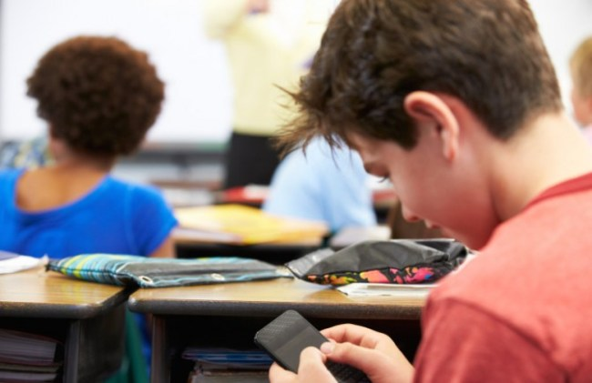 Pupil Sending Text Message On Mobile Phone In Class
