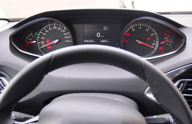 Панель приборов Peugeot 308 с точки зрения водителя: верхнее расположение, руль ничего не перекрывает; широко разнесенные приборы, которые сложно охватить одним взглядом; тахометр с обратной оцифровкой, которая требует привыкания; все внимание практически всегда сосредоточено на центральном дисплее.