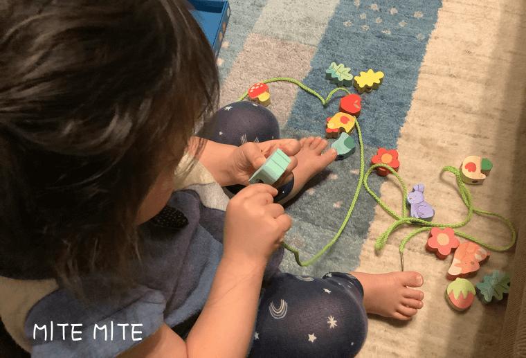 ジェコの紐通しで遊ぶ2歳児