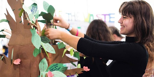 A teacher smiling and putting a green paper leaf on a paper tree.