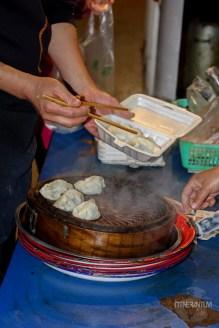 Dumplings cooking in a steamy wooden pot
