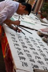 man writing Chinese symbols