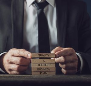 Businessman stacking wooden pegs to assemble a Quality is the best business plan sign.