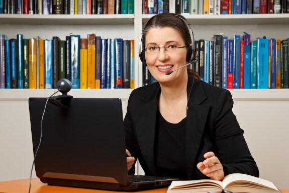 Woman using webcam and headset for online video meeting