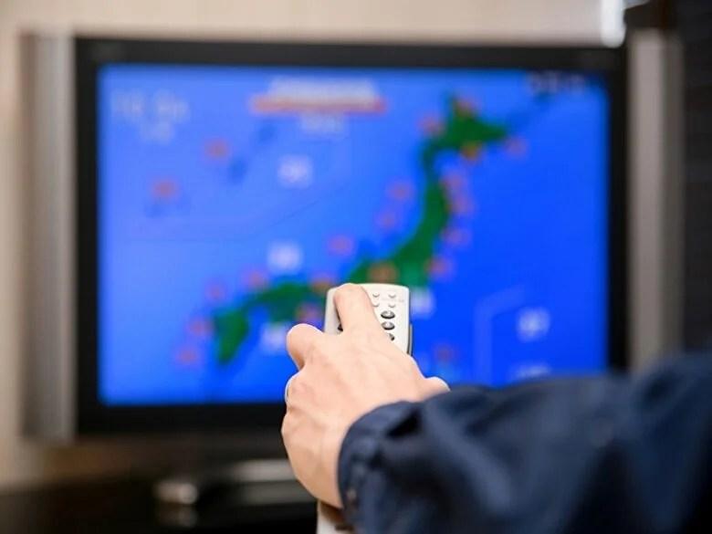 天気予報をテレビで見る男性