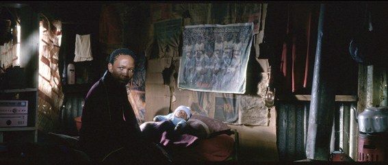 An expressionist image using lighting to emphasise the state of Tostsi with the baby in his shack.