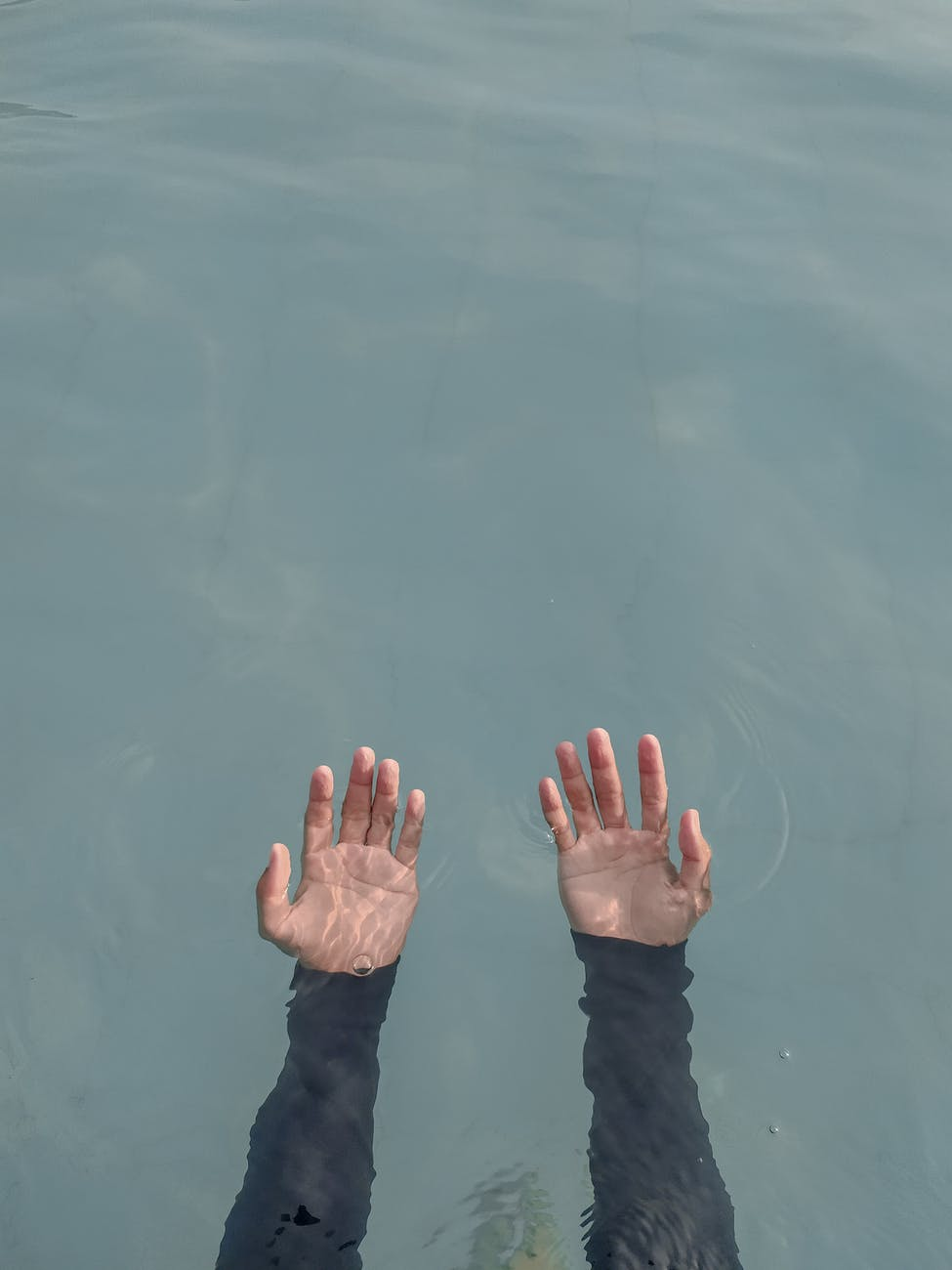person s hand on water