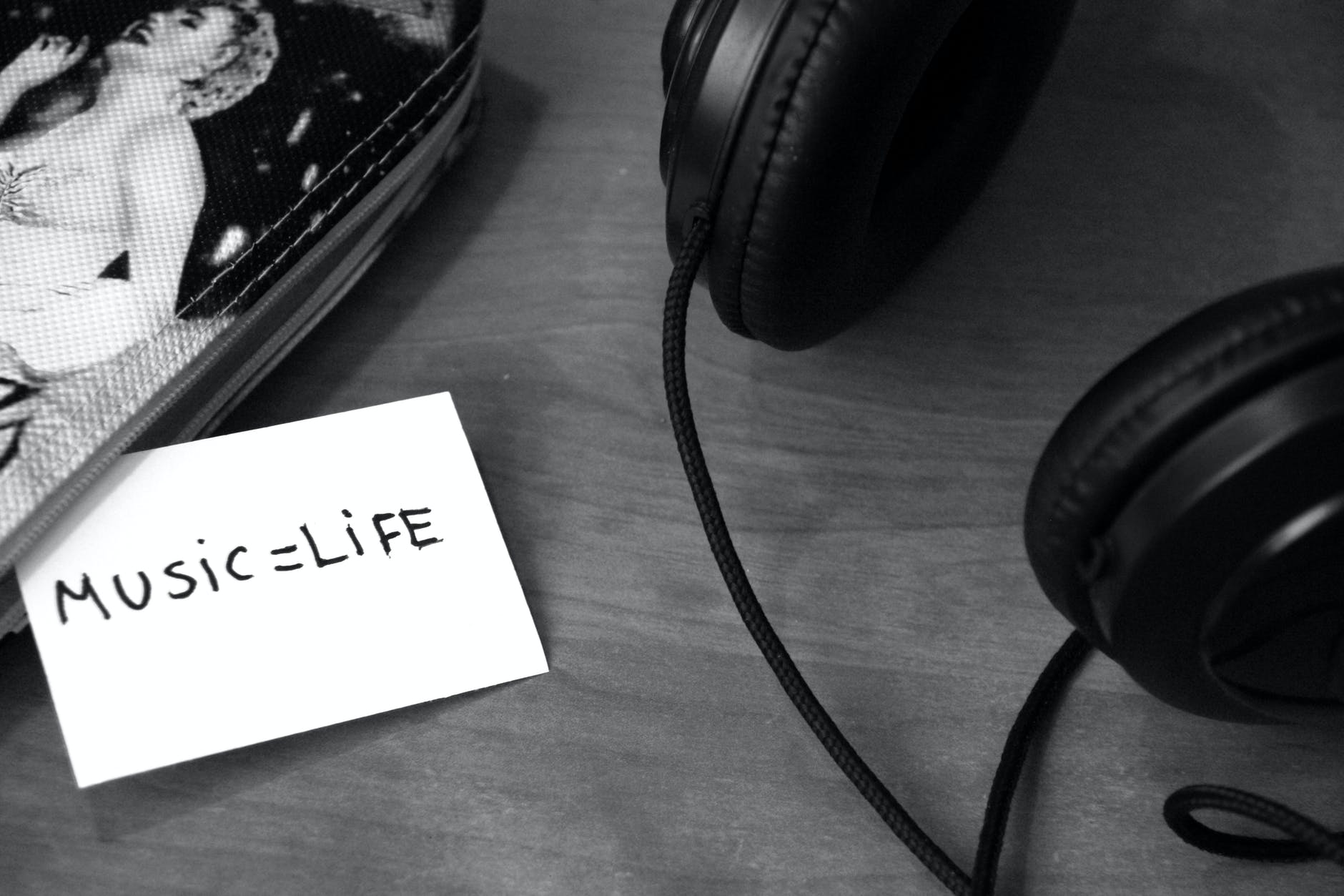 grayscale photo of printer paper with printed music life near headphones