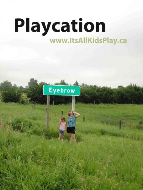 Playcations (Staycations) for families - picture in front of a road sign